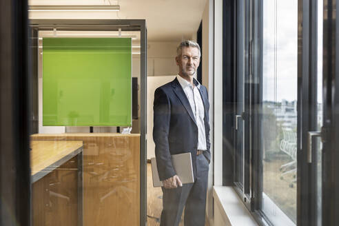 Portrait of confident mature businessman with tablet in office standing at the window - PESF01983