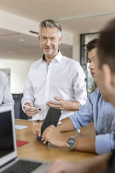 Mature businessman leading a meeting in office - PESF01989