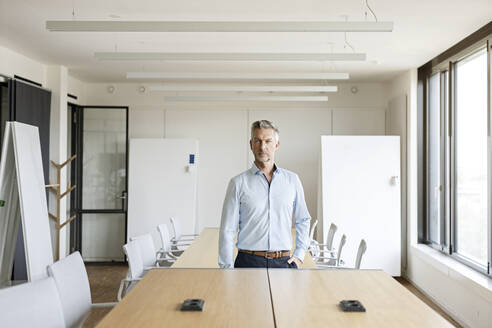 Portrait of confident mature businessman in conference room - PESF01992