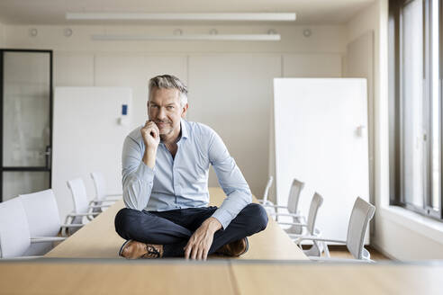 Portrait of confident mature businessman sitting on table in conference room - PESF01995