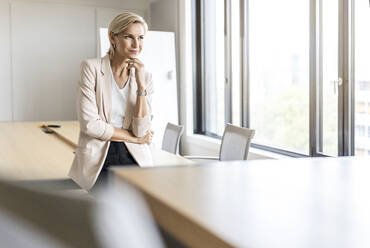 Blond businesswoman in conference room thinking - PESF01998