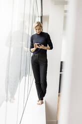 Casual businesswoman using cell phone at the window - PESF02010