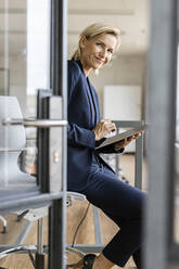 Portrait of smiling blond businesswoman using tablet in conference room - PESF02013