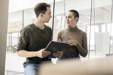 Young woman and man with tablet talking at the window in office - PESF02037