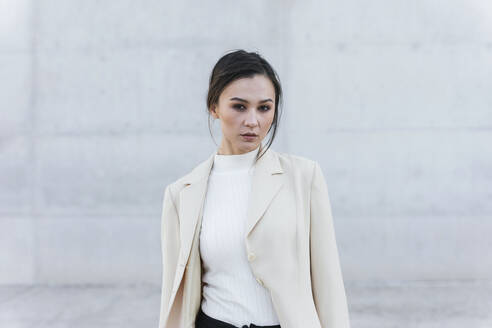 Young woman wearing beige suit standing in front of concrete wall - TCEF00530