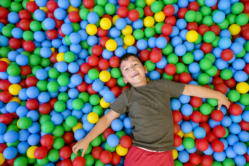Smiling boy lying in ball pit - MGIF00912