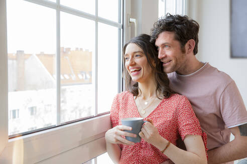 Happy couple at home looking out of window - FKF03746