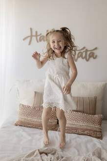 Portrait of happy little girl jumping on bed - GMLF00163