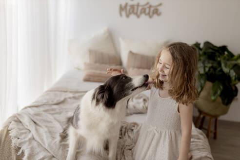 Smiling little girl stroking her dog in bedroom - GMLF00169