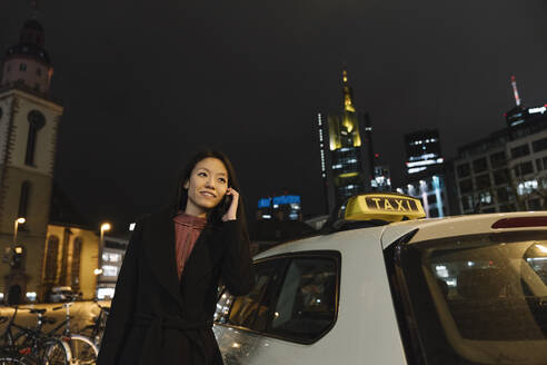 Young woman on the phone next to a taxi in the city at night, Frankfurt, Germany - AHSF02376
