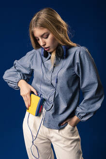 Young blond woman with walkman and headphones in front of blue background - AGGF00057