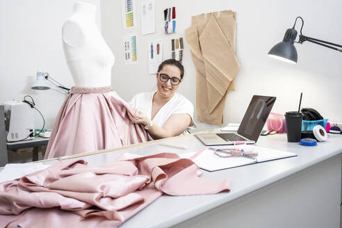 Seamstress working in tailor shop and presenting skirt via video call - VPIF02360