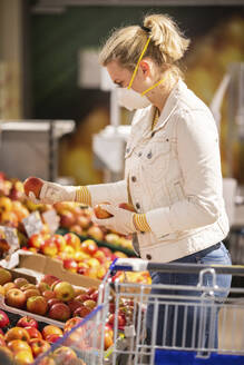 Teenage girl wearing protectice mask and gloves choosing apples at supermarket - ASCF01272