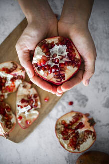 Hands of woman holding halved pomegranate - GIOF08140