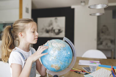 Girl looking at globe at home - HMEF00916