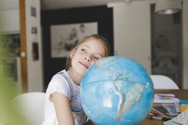 Portrait of daydreaming girl at home leaning on globe - HMEF00919