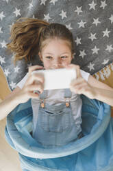 Portrait of smiling girl lying in blue fabric tunnel on the floor at home taking selfie with mobile phone - HMEF00922