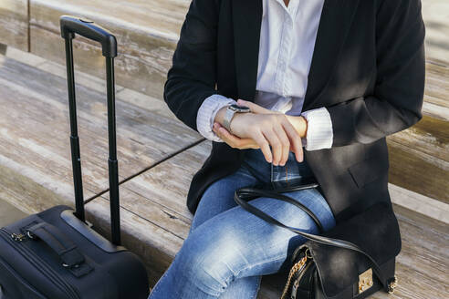 Crop view of young businesswoman with handbag and trolley bag sitting on bench outdoors checking the time - XLGF00118
