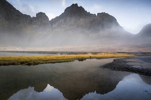 Idyllic view of mountain range reflecting in water against sky at Hvalnes Nature Reserve Beach, Iceland - DAMF00424