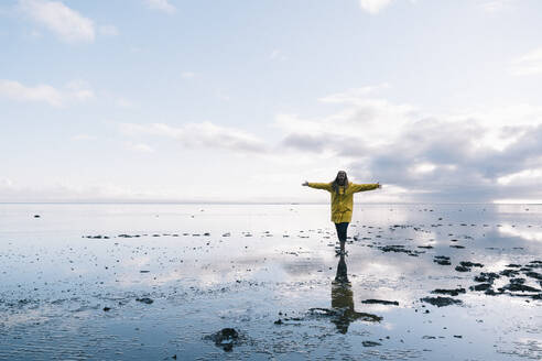 Woman with arms outstretched reflecting in sea at Hvalnes Nature Reserve Beach, Iceland - DAMF00427