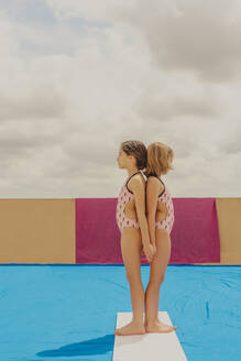 Two girls wearing swimsuits standing back to back with eyes closed outdoors - ERRF03593