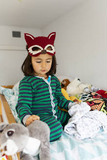 Portrait of little girl with fox mask crouching on bunk bed at home - VABF02842