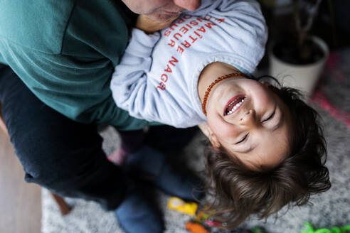 Portrait of happy little girl having fun with her father at home - VABF02848