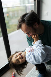 Portrait of happy little girl having fun with her father at home - VABF02851