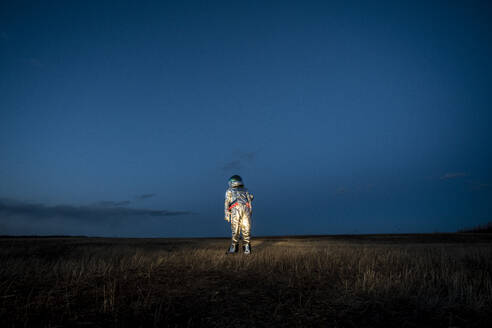 Spacewoman standing on meadow in the evening - VPIF02389
