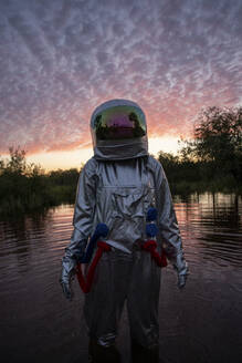 Portrait of spacewoman standing in water at sunset - VPIF02401