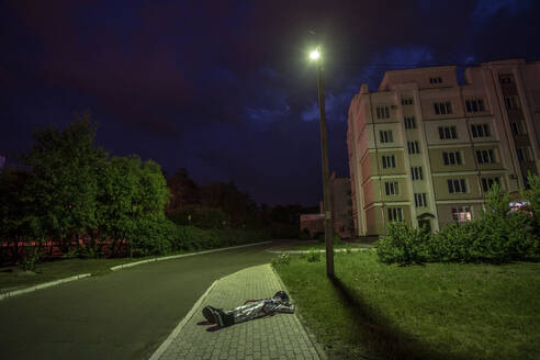 Spaceman resting under street lamp on pavement at night - VPIF02407