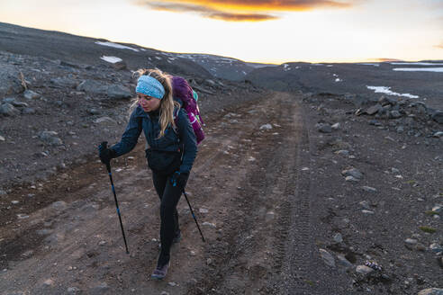 Female Hiker On Dirt Road To Highlands In Remote Iceland Wilderness - CAVF80638