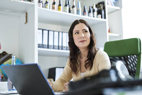 Businesswoman looking away while using laptop at desk in office - MMIF00202