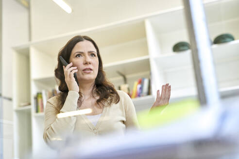 Serious businesswoman talking on mobile phone at workplace - MMIF00211