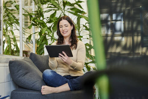 Smiling entrepreneur using digital tablet while sitting on sofa at workplace - MMIF00214