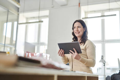 Smiling entrepreneur using digital tablet while standing at desk in workplace - MMIF00217
