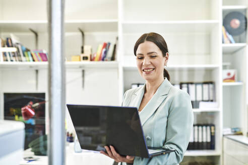Smiling businesswoman in formals using laptop at office - MMIF00226