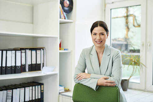 Smiling female entrepreneur with arms crossed at workplace - MMIF00232