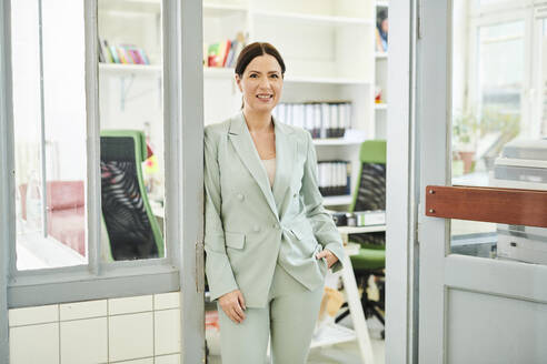 Businesswoman standing with hands in pockets at doorway in office - MMIF00235
