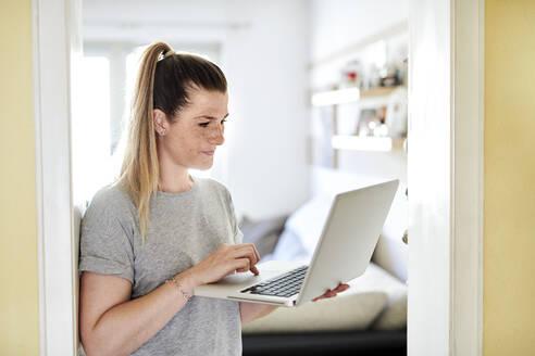 Freelancer using laptop while standing at doorway  in house - MMIF00238