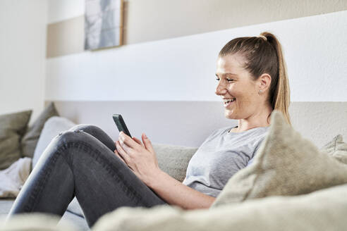 Smiling woman using smart phone while sitting on sofa at home - MMIF00241