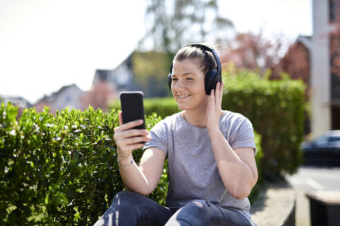 Smiling woman listening music through headphones on smart phone by plants - MMIF00250