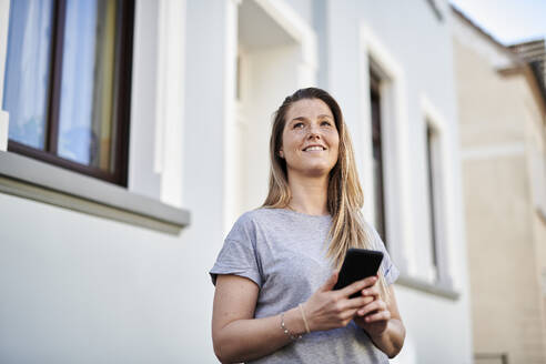 Woman looking away while holding mobile phone against house - MMIF00253