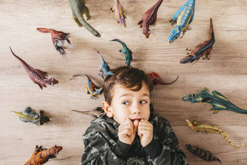 Portrait of anxious little boy lying on the floor between toy dinosaurs - JRFF04403