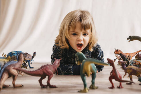 Portrait of little girl lying on the floor playing with toy dinosaurs - JRFF04406