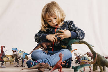 Portrait of little girl sitting on the floor playing with toy dinosaurs - JRFF04409