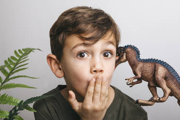 Portrait of little boy with toy dinosaur pulling funny face - JRFF04415