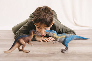 Portrait of little boy crouching on the floor playing with toy dinosaurs - JRFF04418