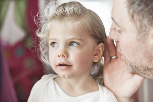 Father whispering in dauthter's ear - SDAHF00779