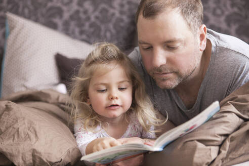 Father and daughter reading a book in bed - SDAHF00782